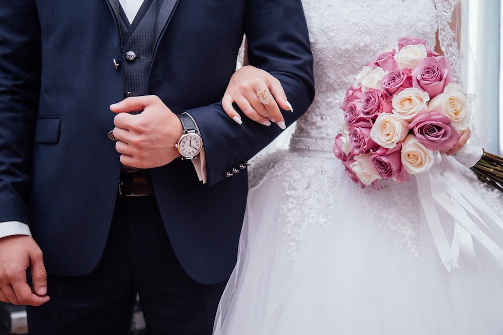Man and woman linking arms on wedding day